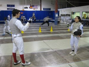 Junior Cooper Jackson fences with Day eighth grader Tiffany Luong last Tuesday at the Boston Fencing Club in Waltham.