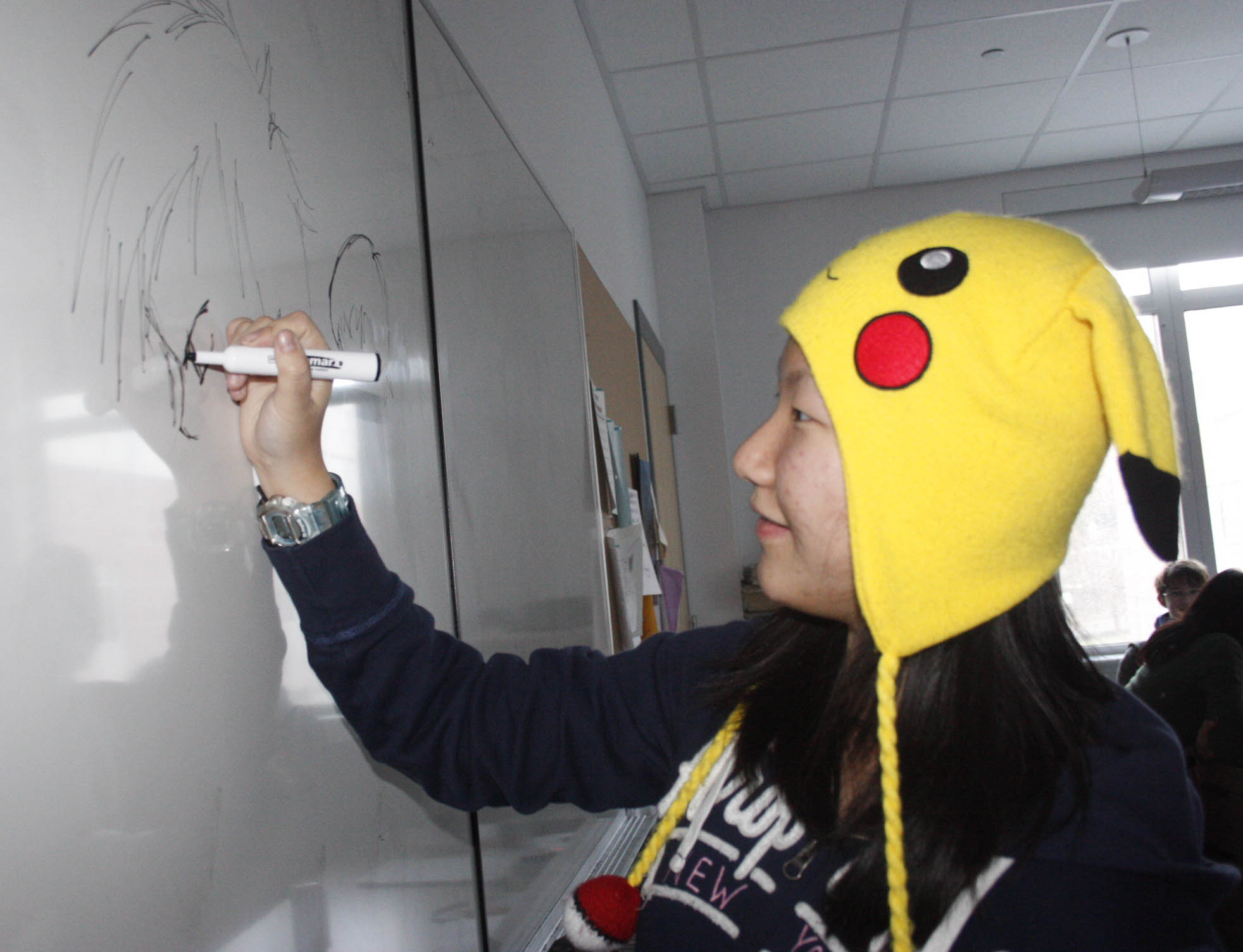 Freshman Joanna Le draws on the white board during Japanese film and anime club.