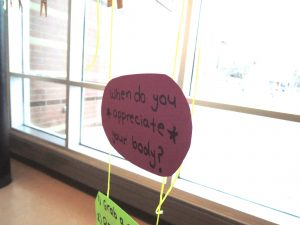 Students hung neon note cards with the answer to this question on clotheslines outside the auditorium.