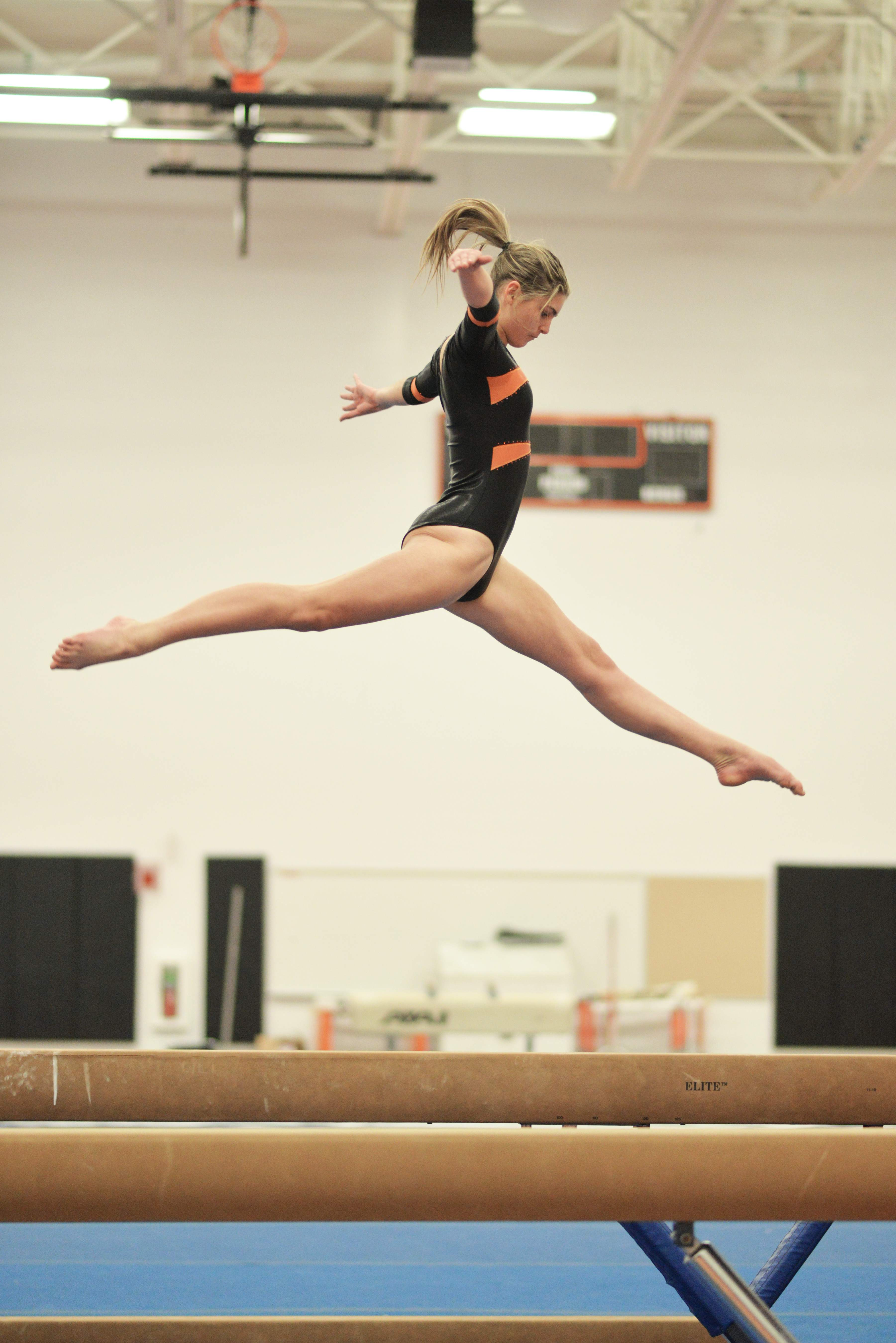 Sophomore Calley Dias performs a split leap during her beam routine Jan. 7 against Framingham. Photo by Judith Gibson-Okunieff.
