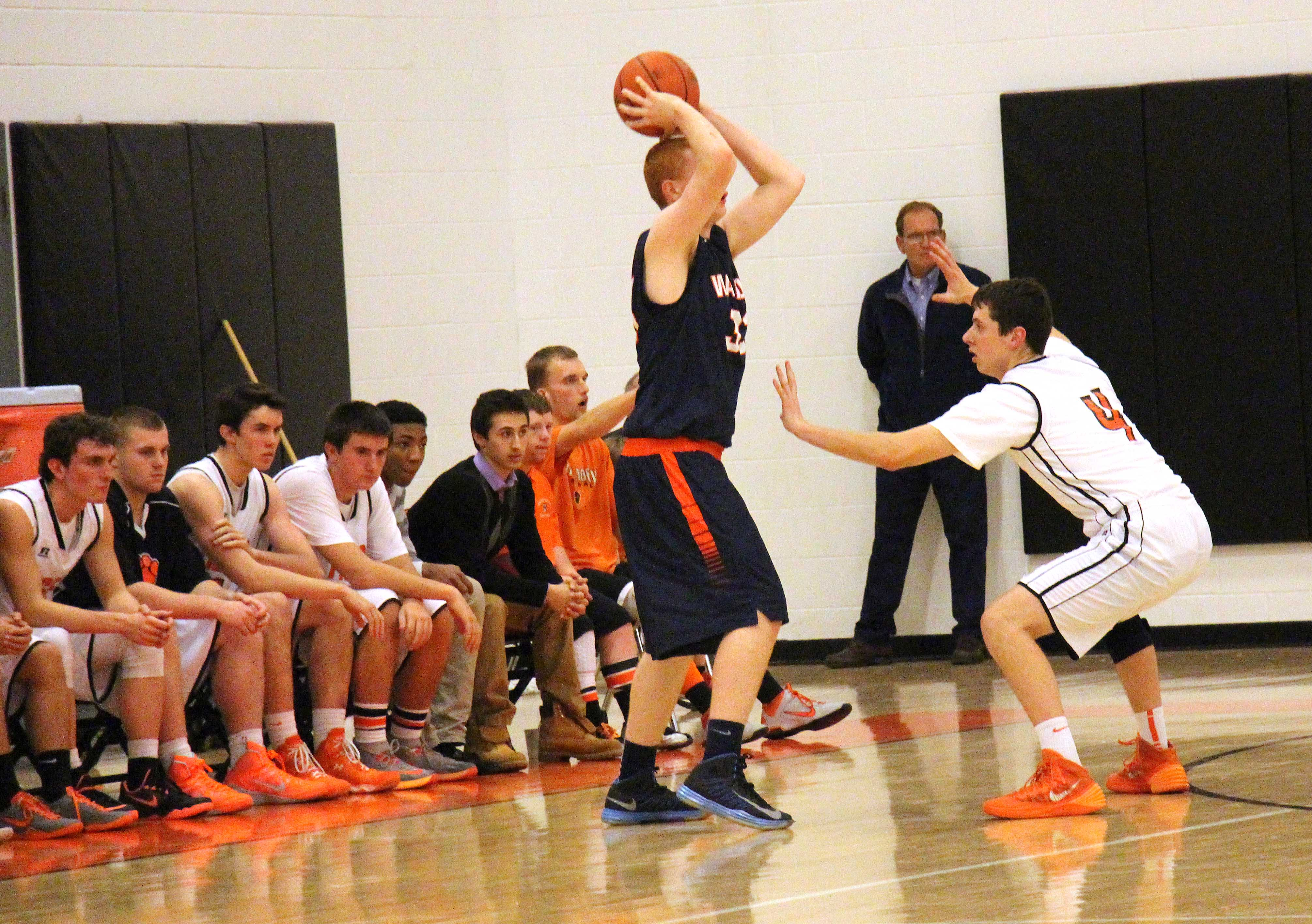 Senior Brett Stanton defends a Natick forward during the Tigers' 109-52 win over the Red Hawks.